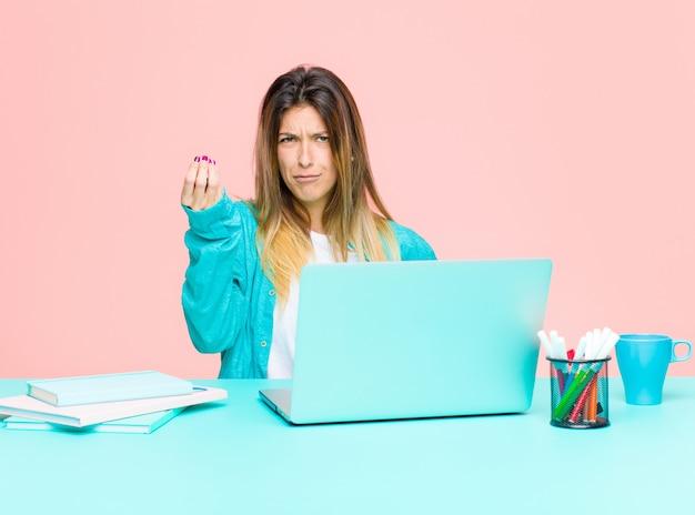 Jovens bonitas mulher trabalhando com um laptop fazendo capice ou dinheiro gesto, dizendo para você pagar suas dívidas!