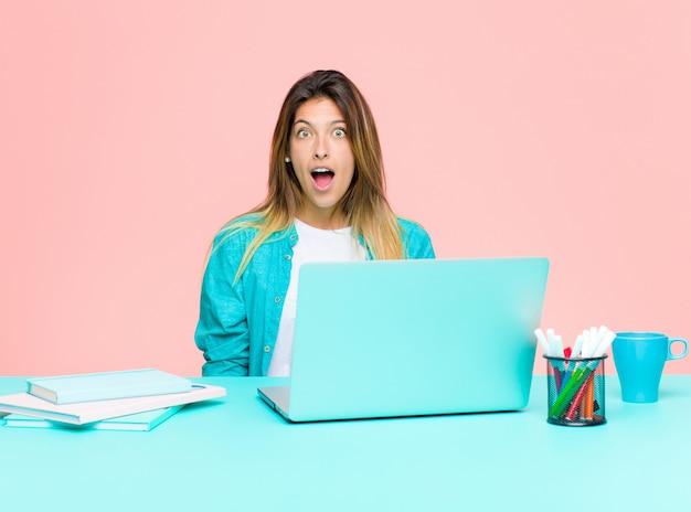 Jovens bonitas mulher trabalhando com um laptop olhando muito chocado ou surpreso, olhando com a boca aberta dizendo uau