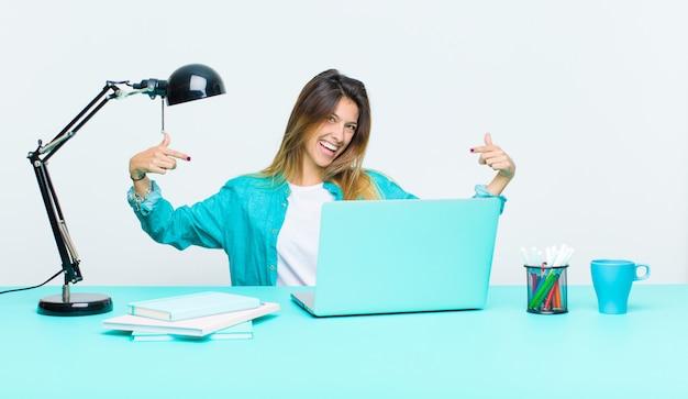 Jovens bonitas mulher trabalhando com um laptop olhando orgulhoso, arrogante, feliz, surpreso e satisfeito, apontando para si mesmo, sentindo-se um vencedor