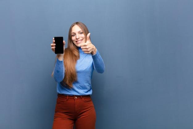 Jovens bonitas mulher usando um telefone inteligente contra a parede azul com um espaço de cópia