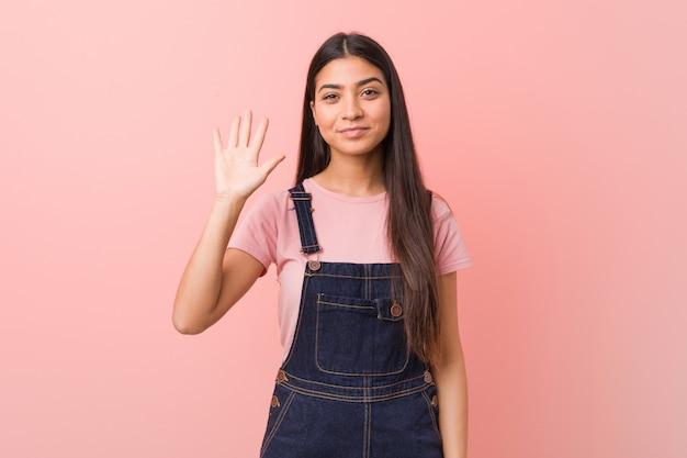 Jovens bonitas mulher vestindo um jeans dungaree sorrindo alegre mostrando número cinco com os dedos