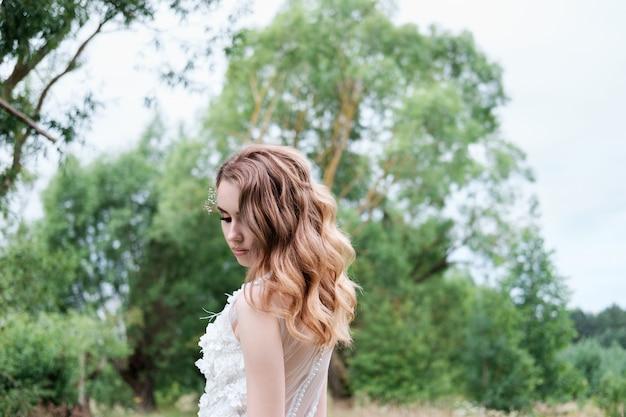 Jovens bonitas noiva vestido de noiva branco ao ar livre, maquiagem e penteado