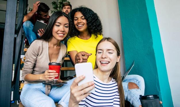 Jovens bonitos estão passando um tempo juntos. os alunos estão estudando na universidade. lendo um livro, trabalhando com um laptop e se comunicando enquanto está sentado na escada