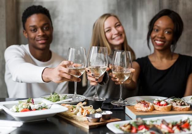 Jovens bonitos que comem o vinho e o jantar