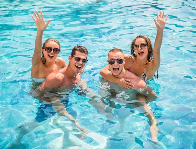 Jovens bonitos que têm o divertimento na piscina.