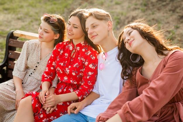 Jovens bonitos sentam-se em um banco no verão