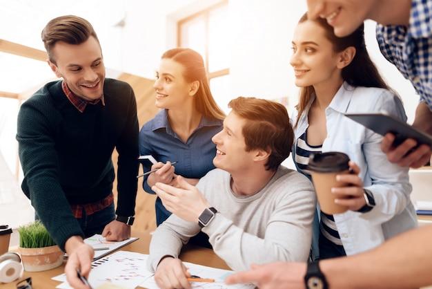 Jovens brainstorms novo plano no escritório de espaço aberto.