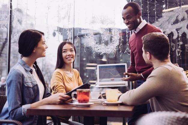 Jovens brotando quatro colegas almoçam enquanto conversam e desenvolvem o plano