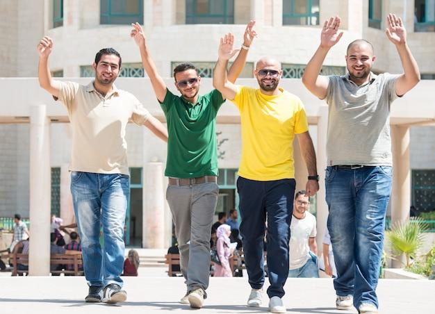 Jovens caminhando juntos com os braços para cima