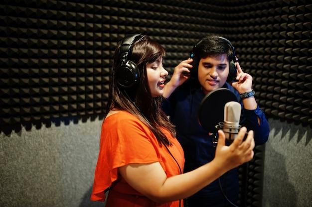 Jovens cantores asiáticos gravando no estúdio