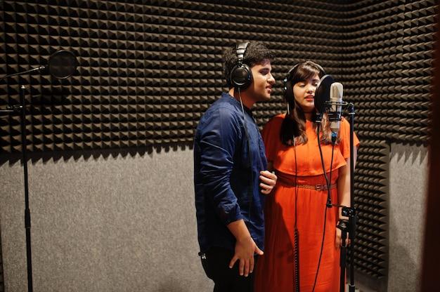 Jovens cantores de duetos asiáticos gravando em estúdio