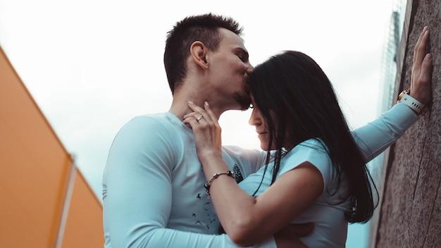 Jovens casais apaixonados em pé perto da parede de tijolos, felizes e satisfeitos