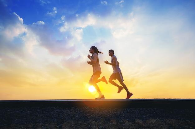 Jovens casais correndo correndo na estrada. fit runner fitness runner durante exercícios ao ar livre com o pôr do sol