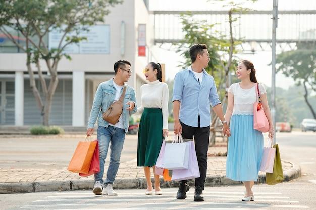 Jovens casais vietnamitas alegres de mãos dadas ao atravessar a rua com sacolas de compras nas mãos
