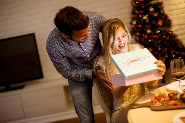 Jovens celebrando o natal e abrindo presentes na sala