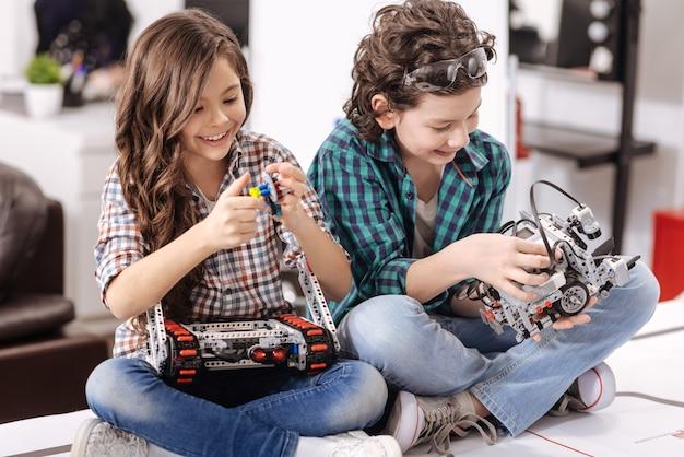 Jovens cientistas cooperando. crianças sorrindo alegres e encantadas sentadas em casa testando gadgets e dispositivos enquanto expressam alegria