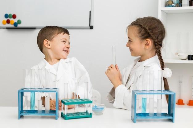 Jovens cientistas fofos com tubos de ensaio e jalecos