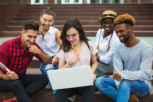 Jovens colaborando com laptop