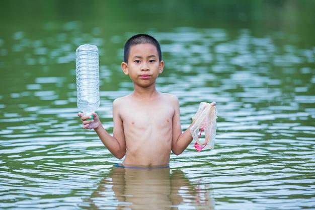 Jovens colecionam lixo no rio, conceito do dia nacional da juventude e dia mundial do meio ambiente.