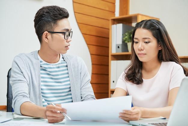 Jovens colegas asiáticos trabalhando com documentos
