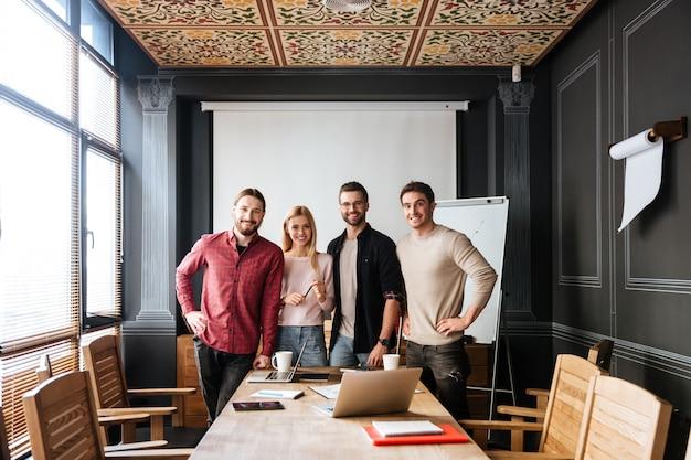 Jovens colegas atraentes em pé e coworking