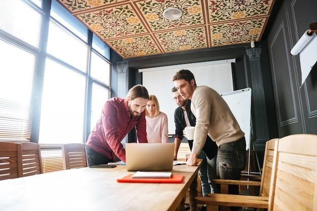 Jovens colegas atraentes em pé enquanto trabalha com laptop