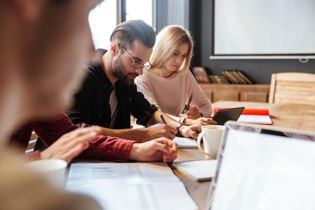 Jovens colegas atraentes sentado no escritório e coworking.