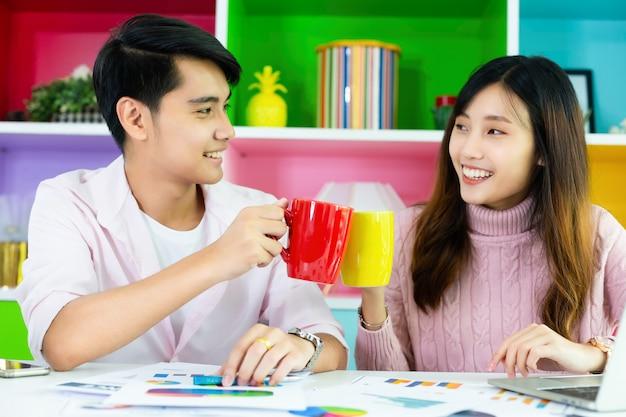Jovens colegas bebendo bebidas durante o trabalho