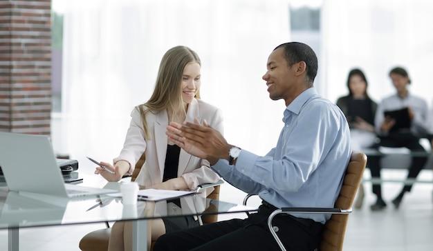 Jovens colegas de trabalho conversando atrás de uma mesa