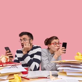 Jovens colegas de trabalho sentados à mesa com documentos Foto gratuita