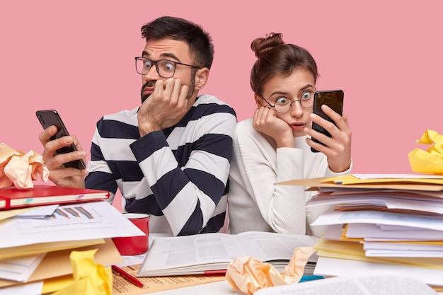 Jovens colegas de trabalho sentados à mesa com documentos