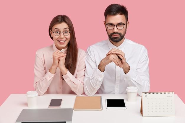 Jovens colegas de trabalho sentados à mesa com gadgets e calendário