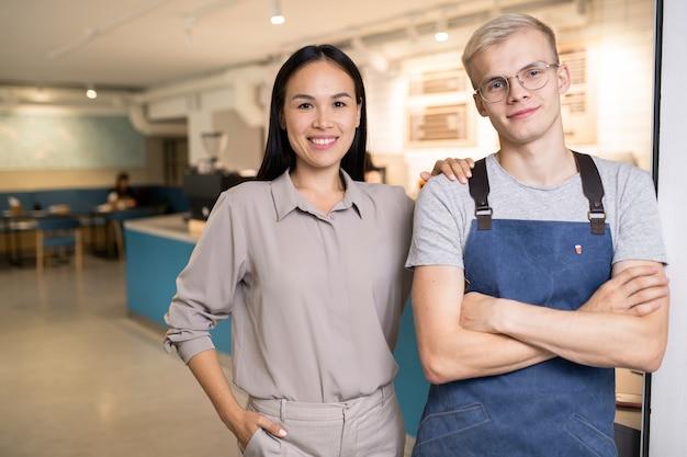 Jovens colegas interculturais felizes em trajes de trabalho olhando para você enquanto está dentro de um café ou restaurante moderno