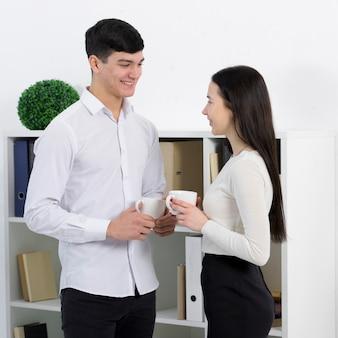 Jovens colegas masculinos e femininos, tomando um café no escritório