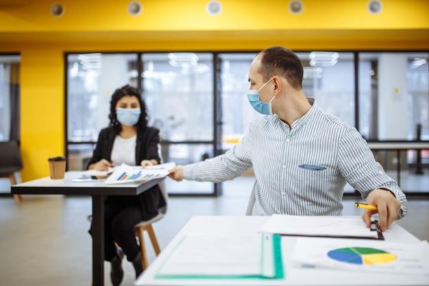 Jovens colegas passam documentos uns para os outros que trabalham em um escritório durante o surto da pandemia de coronavuris.