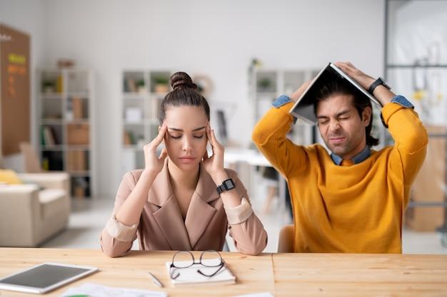 Jovens colegas perplexos, cansados do trabalho sentados à mesa e com dor de cabeça, problema com o projeto por causa do coronavírus