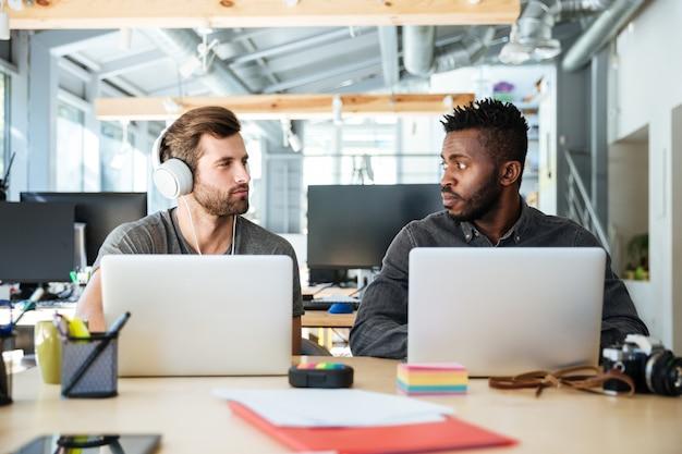 Jovens colegas sérios sentado no escritório de coworking