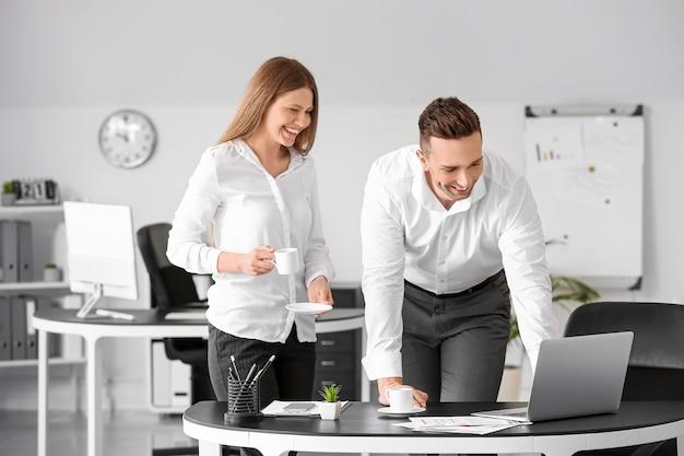 Jovens colegas tomando café enquanto trabalham no escritório