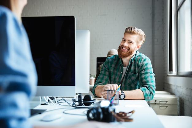 Jovens colegas trabalham no escritório usando computadores