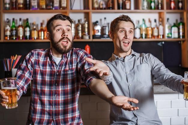 Jovens com cerveja assistindo futebol em um bar