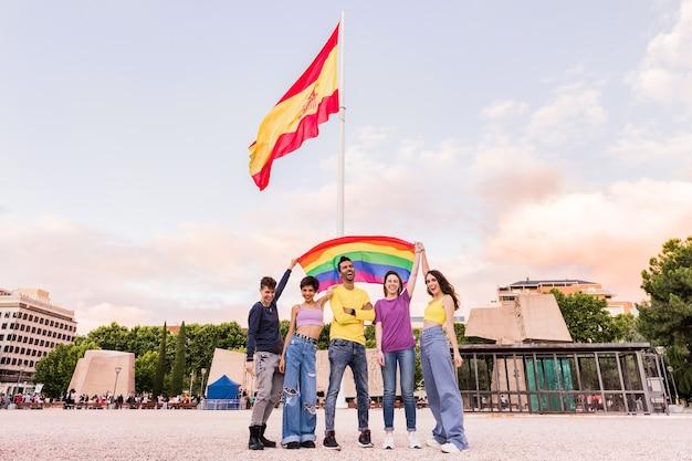 Jovens com diversidade étnica e grupos lgbtq mistos de gêneros felizes com a bandeira do arco-íris