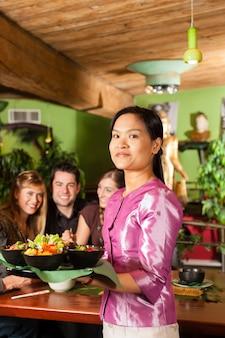 Jovens com garçonete comendo no restaurante tailandês