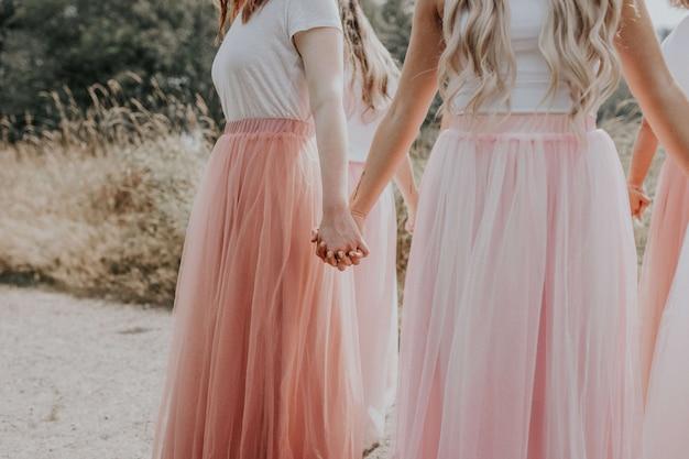 Jovens com lindos vestidos de mãos dadas