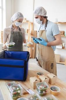 Jovens com máscaras protetoras e luvas, embalando alimentos orgânicos em sacolas e entregando os alimentos