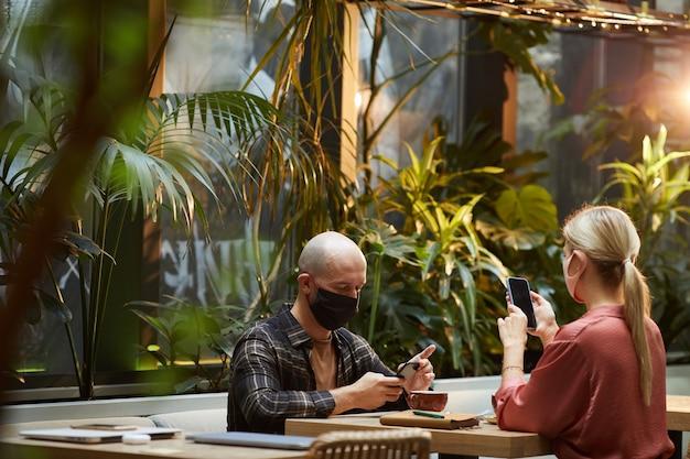 Jovens com máscaras protetoras trabalhando on-line no celular, sentados em um café