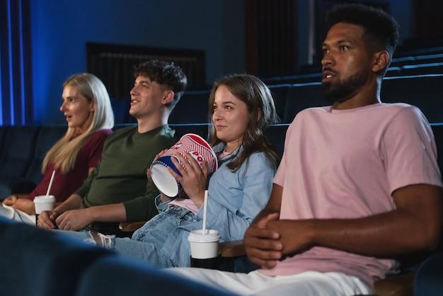 Jovens com pipoca e drinques no cinema assistindo filme de suspense