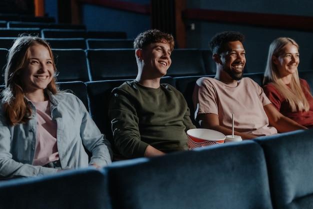 Jovens com pipoca no cinema assistindo filme de suspense