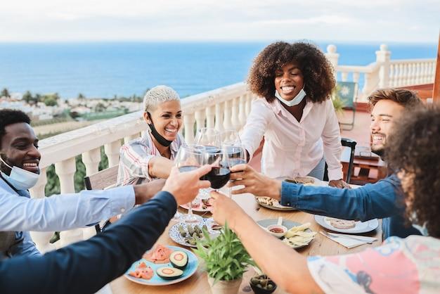 Jovens comemorando com vinho e usando máscaras protetoras