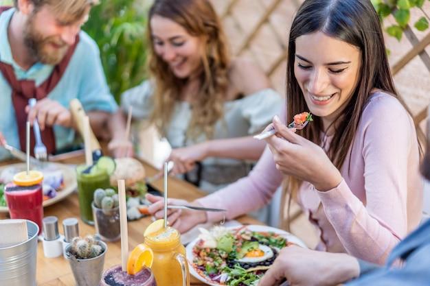 Jovens comendo brunch e bebendo suco batem no bar vintage. pessoas felizes, tendo um almoço saudável e conversando no restaurante da moda