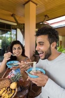 Jovens comendo macarrão chinês feliz sorrindo